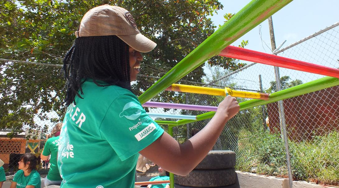 Youth Development volunteer paints a playground jungle gym in Jamaica.